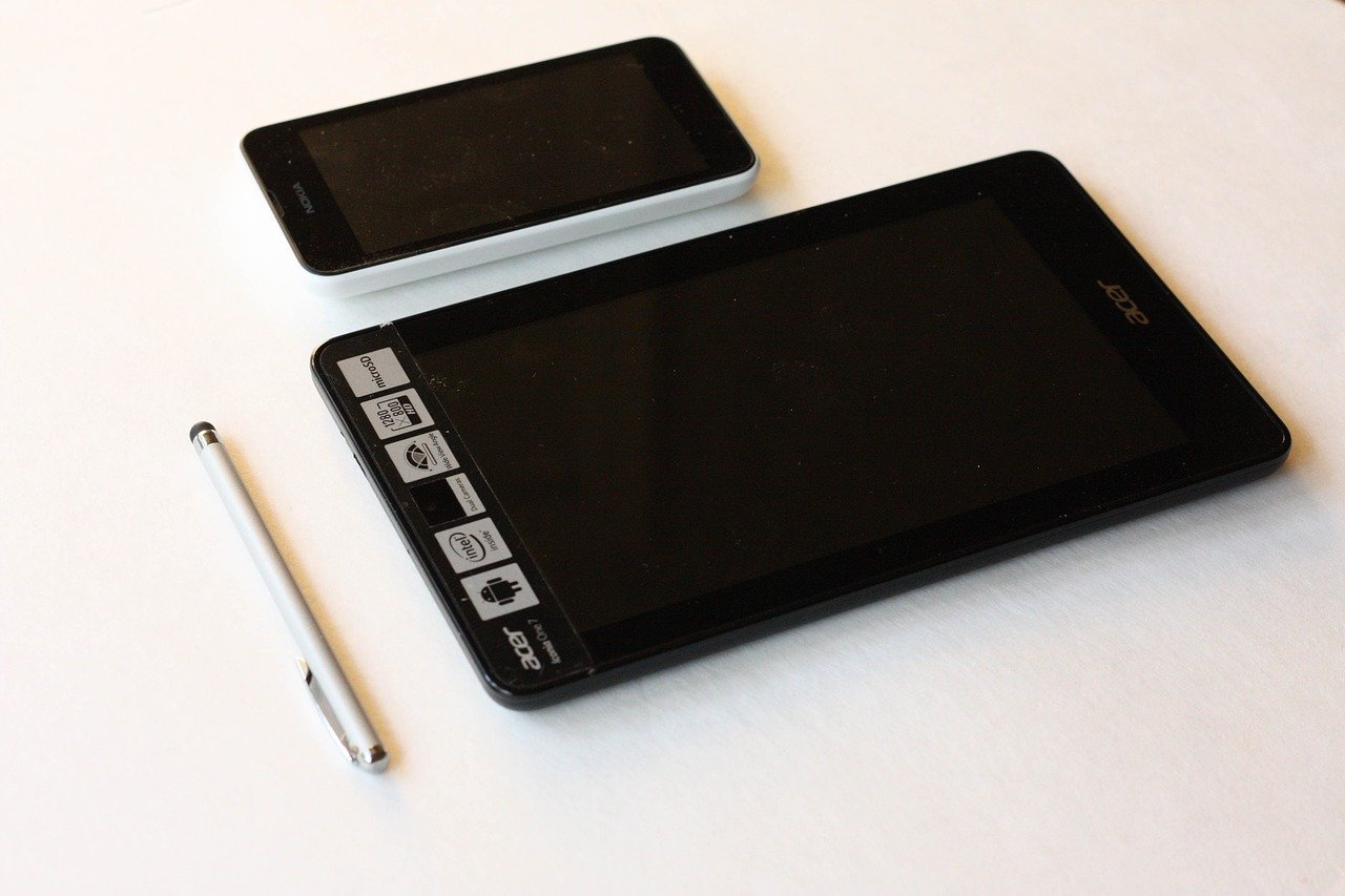 mobile phone with tablet and pen isolated on table