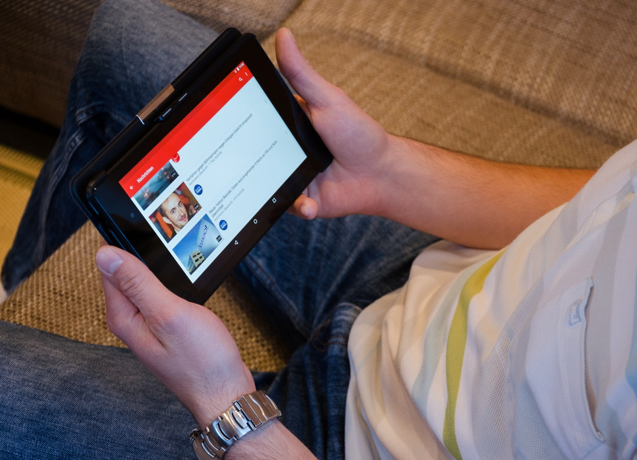 person holding tablet and watching videos on youtube