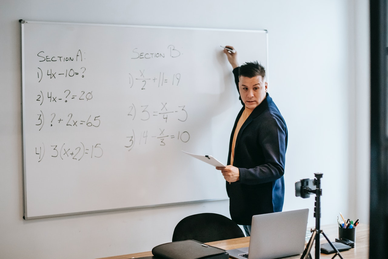 male teacher teaching his students on white board in the classroom